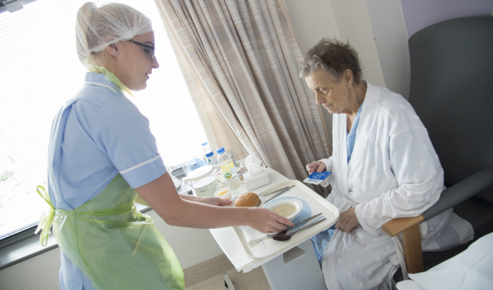 Healthcare assistant serving lunch to patient