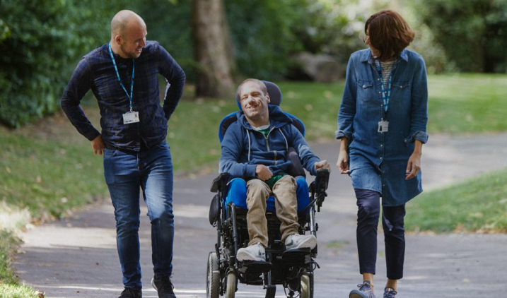 Two nurses talking to man in wheelchair