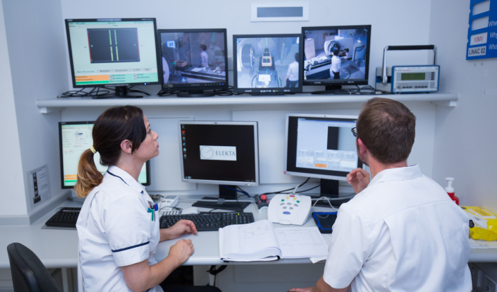 Therapeutic radiographers monitoring treatment on computer screens