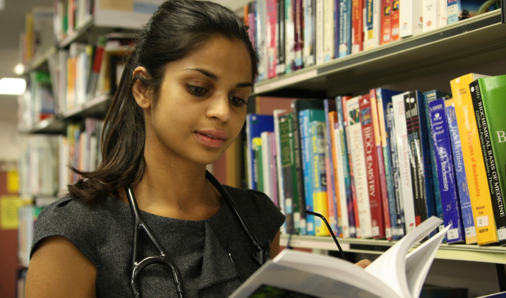 Female doctor reading book in library