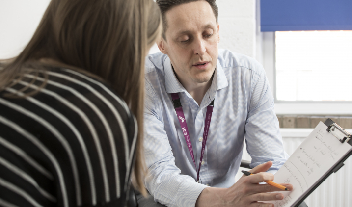 Male support worker talking to female client