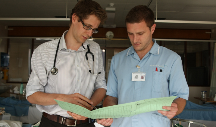 Male trainee and male nurse looking at patient file