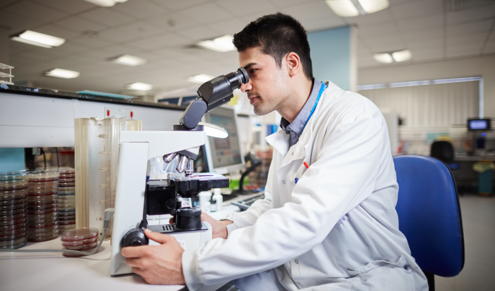 Healthcare scientist with microscope
