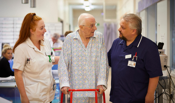male and female nurse with elderly patient in hospital corridor